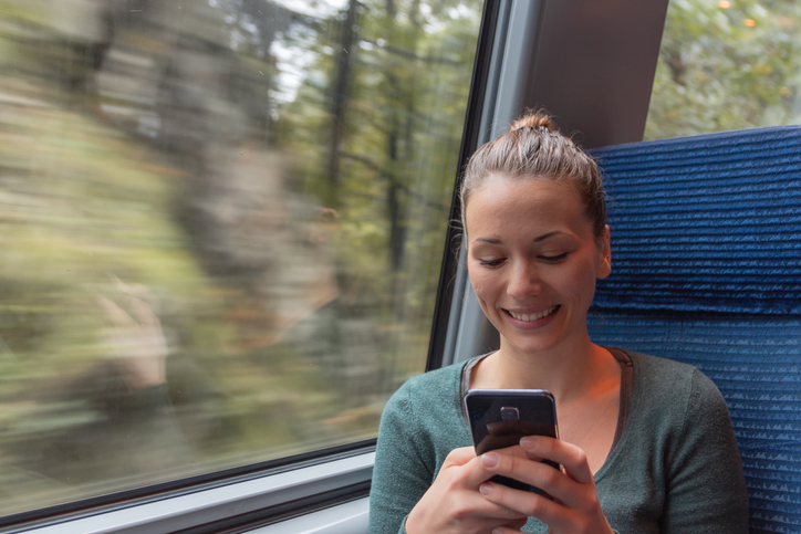 young woman text messaging with his smartphone during a journey in the train while she is going to work